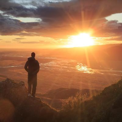 Man stood on mountainside looking at sunset