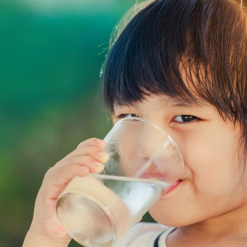 Young girl drinking a glass of water